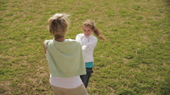 Grandmother and granddaughter twirling around in park. Stock Footage