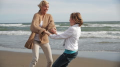 Grandmother and granddaughter twirling together on windy beach. Stock Footage