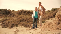 Grandmother and granddaughter running together to sea on windy beach. - stock footage