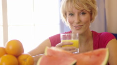 Dolly shot of woman with fruit in foreground drinking glass of orange juice. - stock footage