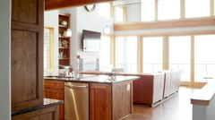 Pan left to right of a large living room and kitchen in a modern house Stock Footage