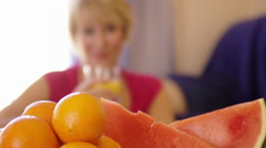 Rack focus shot of woman with fruit in foreground drinking glass of orange Stock Footage