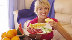 Dolly shot of woman with healthy fruit plate eating an apple. - stock footage
