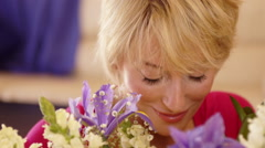 Close up dolly shot of woman smelling flower scent. - stock footage