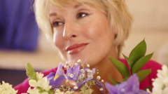 Close up dolly shot of woman smelling flower scent. Stock Footage