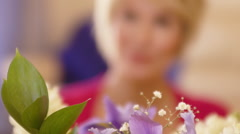 Rack focus shot of woman with flower arrangement. - stock footage