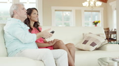 A man turns off the TV while sitting on the couch with a woman, then they hug Stock Footage