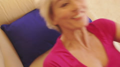 Woman falling back on sofa and laughing. - stock footage