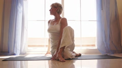Dolly shot of woman practicing yoga in front of window at home. - stock footage