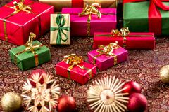 christmas gifts on richly textured cloth. - stock photo