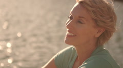Close up of woman sitting by lake and drinking from bottle of water. Stock Footage