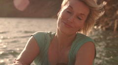 Dolly shot of woman sitting by lakeside relaxing. Stock Footage
