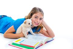 kid girl with puppy chihuahua pet dog at homework - stock photo