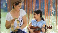 Asian daughter playing ukulele with her mother in park - stock footage