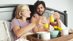 Stock Video Footage of A topless man sits in bed with a woman and they drink juice together