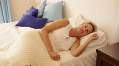 Dolly shot of woman in bedroom waking up and stretching. - stock footage