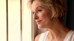 Dolly shot of woman in bedroom standing by window. Stock Footage