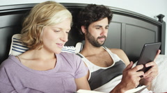 Young couple lays in bed, the woman reads a book and the man looks at a tablet Stock Footage