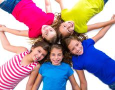 Stock Photo of happy kid girls group smiling aerial view lying circle