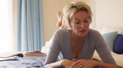 Dolly shot of woman in bedroom lying on bed and reading. Stock Footage