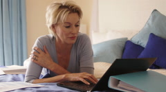Dolly shot of woman in bedroom lying on bed and working on computer. Stock Footage