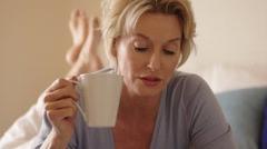 Dolly shot of woman in bedroom lying on bed reading and drinking beverage. Stock Footage