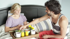 A man has breakfast in bed with his wife and they both drink juice Stock Footage