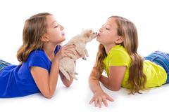 happy twin sister kid girls kissing puppy dog lying - stock photo