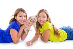 happy twin sister kid girls and puppy dog lying - stock photo