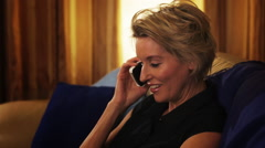 Dolly shot of woman relaxing on sofa in the evening, answering phone. Stock Footage