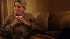 Rack focus dolly shot of woman on sofa with beverage through rainy window. Stock Footage