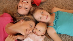 Four generations of females lying on rug together. - stock footage