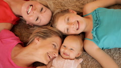 Overhead shot of four generations of females lying on rug together. - stock footage