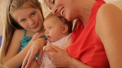 Grandmother and two granddaughters together on sofa. Stock Footage
