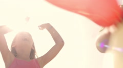 Slow motion of children playing on beach holding balloons. - stock footage