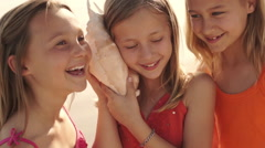 Three girls playing on beach listening to conch shell. - stock footage