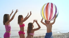 Slow motion of five children playing with beach ball on beach. - stock footage