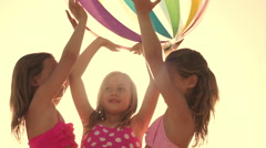 Slow motion of three children playing with beach ball on beach. - stock footage