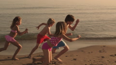 Five children running away from camera on beach. - stock footage
