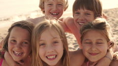 Close up of five children on beach facing camera and laughing. Stock Footage
