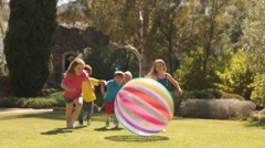 Five children pushing beach ball towards camera in park. - stock footage