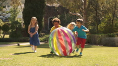 Slow motion of five children pushing beach ball towards camera in park. - stock footage