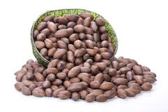 unshelled pecan nuts spilling from zulu beaded basket - stock photo