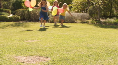 Lift up of three girls running towards camera with balloons. Stock Footage