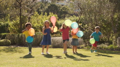 Slow motion of five children running towards camera with balloons. Stock Footage