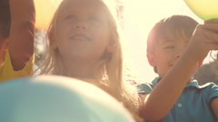 Five children playing in park with balloons. Stock Footage