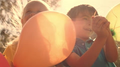 Five children playing in park with balloons. - stock footage