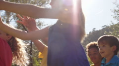 Five children playing with bubbles in park. - stock footage
