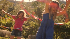 Two children playing with hula hoop in park. - stock footage