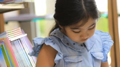 Little Asian girl reading a cartoon book in library - stock footage